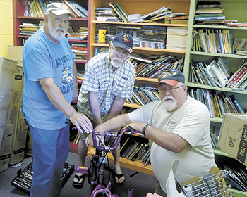 Volunteers assemble bicycles...