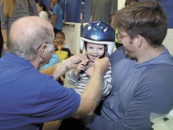 Children receive helmets during Brain Bonanza