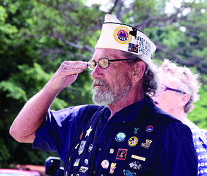 Randy Robbins a Vietnam Veteran salutes during the National Anthem