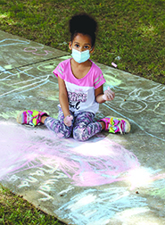Tiana Accor colors the sidewalk during Chalk Fest