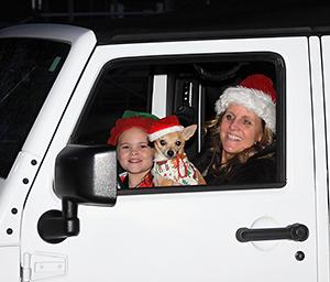 Julia Baker (age 6), Dog Oliver and Jami Bumgarner talk to Santa at the Shelby City Park Carrousel Christmas Drive -Thru.