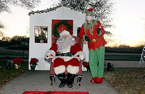 Santa and Elf Lydia Eaker await anxious kids at the Shelby City Park Carrousel Christmas Drive -Thru